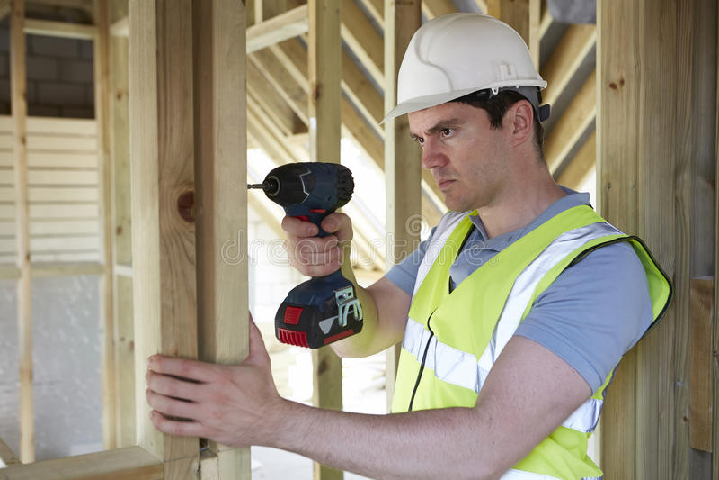 Byggnadsarbetare Using Cordless Drill på husbyggande arkivfoton