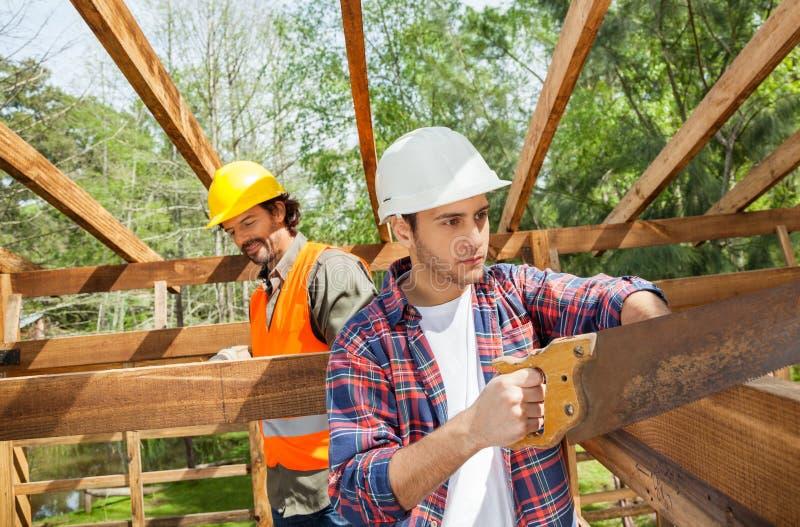 ByggnadsarbetareCutting Wood With Handsaw på arkivbild
