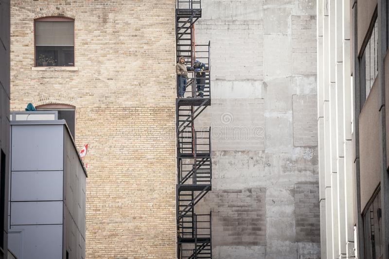 Byggnadsarbetarefixandebrand att fly rostig trappa och stegar, i metall, på typisk norr - amerikansk gammal tegelstenbyggnad fotografering för bildbyråer