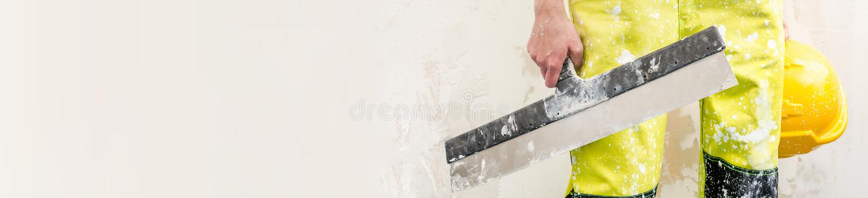Byggnadsarbetareinnehavspackel och hardhat kantjusterad bild arkivbild