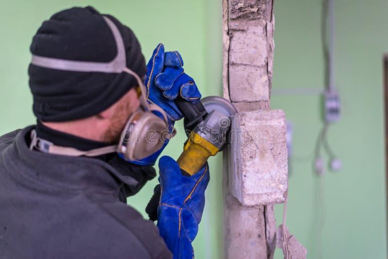 Byggnadsarbetareklippbetongvägg, genom att använda den elektriska skäraren arkivfoton