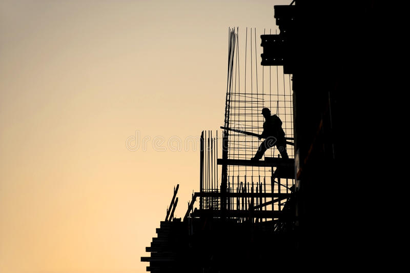 Byggnadsarbetarekontur på solnedgången royaltyfri fotografi