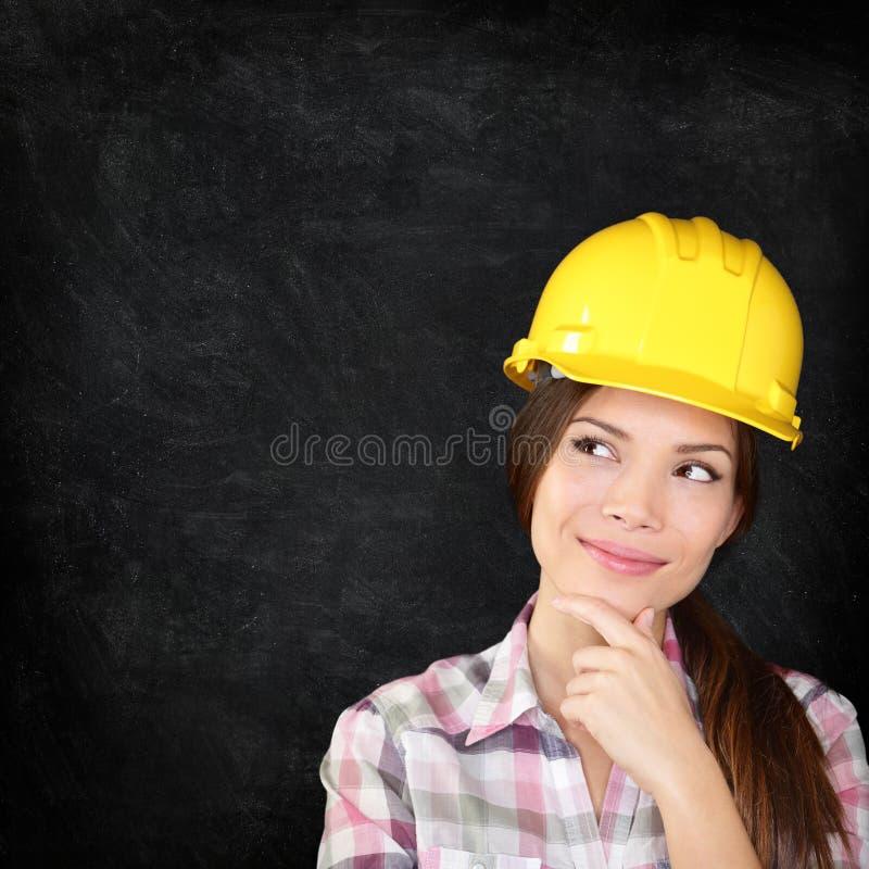 Byggnadsarbetarekvinna på svart tavlatextur arkivfoton
