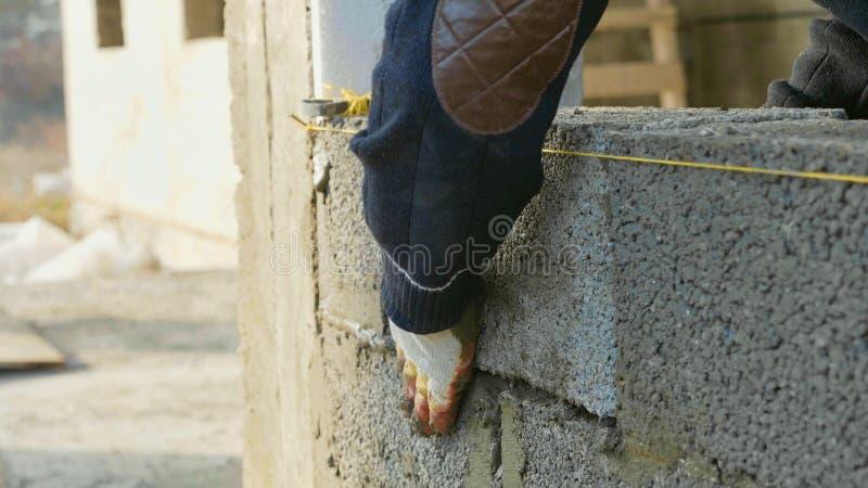 Byggnadsarbetaren bygger tegelstenväggen, closeupsikt på konstruktionsplatsen arkivbild