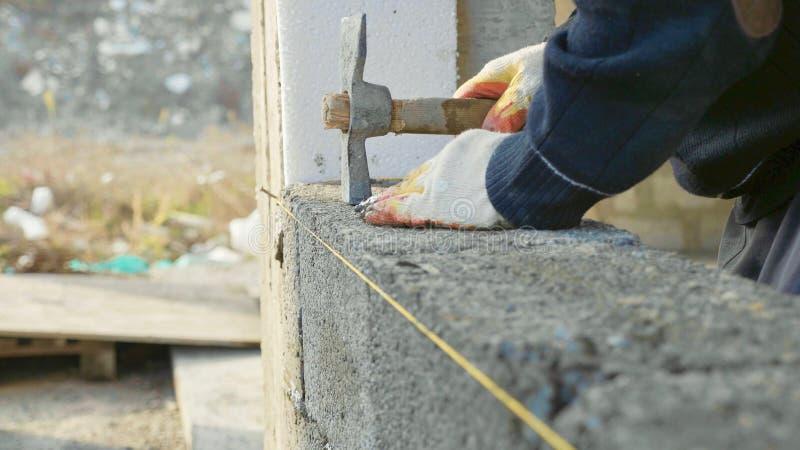 Byggnadsarbetaren bygger tegelstenväggen, closeupsikt på konstruktionsplatsen royaltyfria bilder