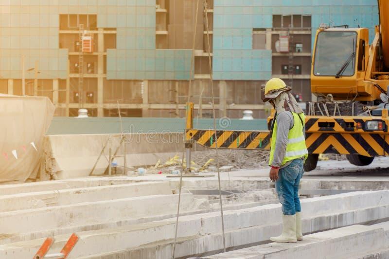 Byggnadsarbetaren i den gr?na waistcoaten och den gula hj?lmen och ett svart maskeringsanseende p? st?lstr?len i royaltyfria bilder