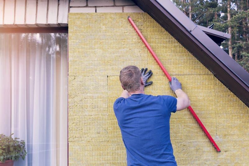 Byggnadsarbetaren kontrollerar nivån av den isolerade husväggen arkivfoto
