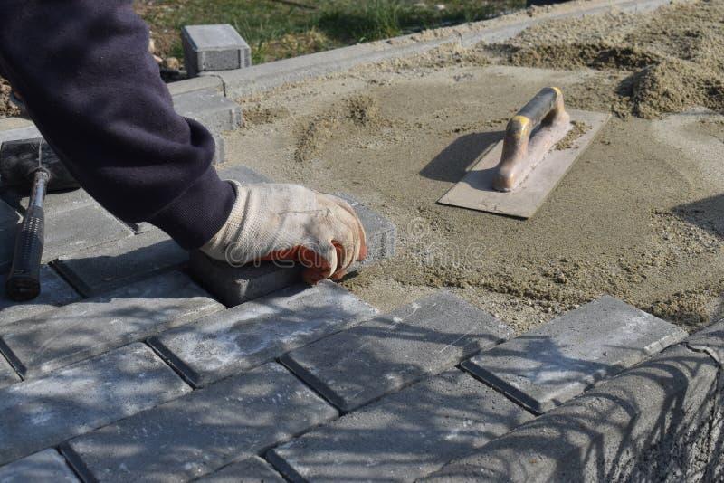 Byggnadsarbetaren lägger stenen för konkret trottoar för vandringsledarbete på konstruktionsplatsen Arbetaren f?r den f?rberedand arkivfoton