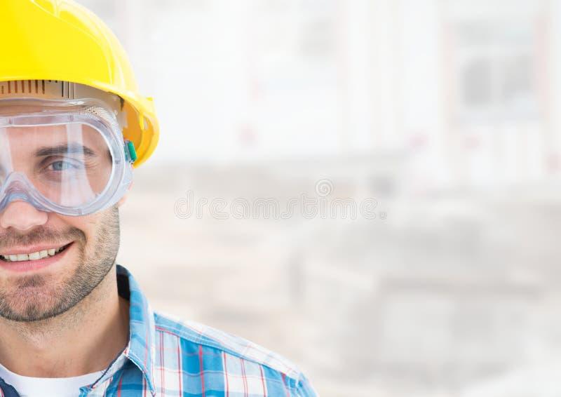 Byggnadsarbetaren med ögonskydd rullar med ögonen framme av konstruktionsplats royaltyfri foto