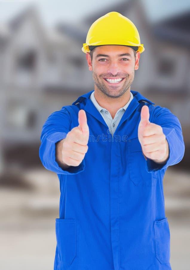 Byggnadsarbetaren med tummar up framme av konstruktionsplats arkivbild