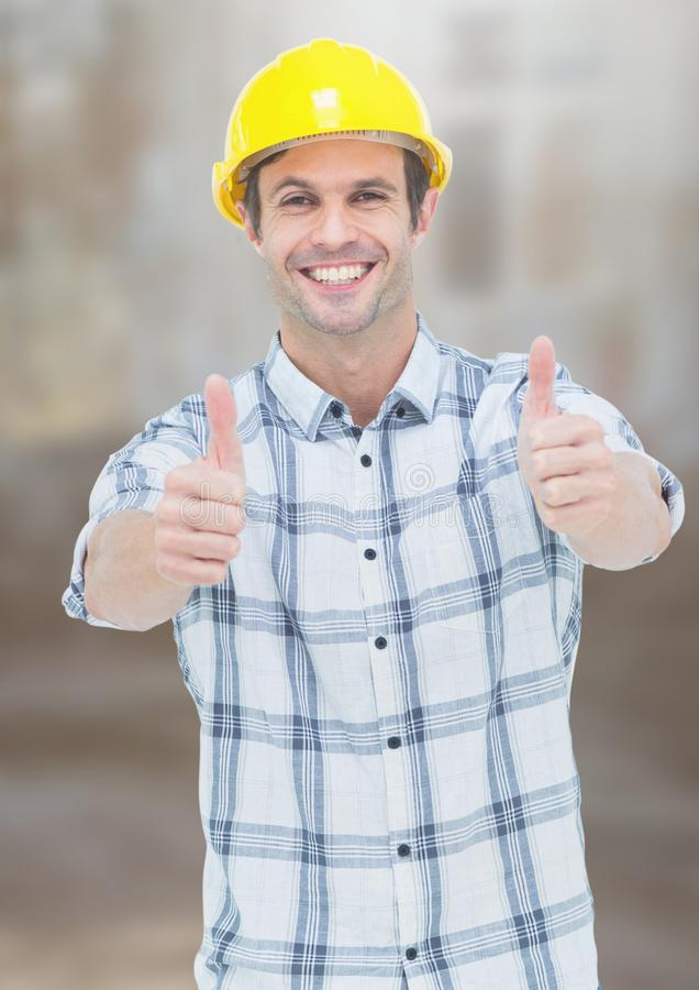 Byggnadsarbetaren med tummar up framme av konstruktionsplats arkivbilder