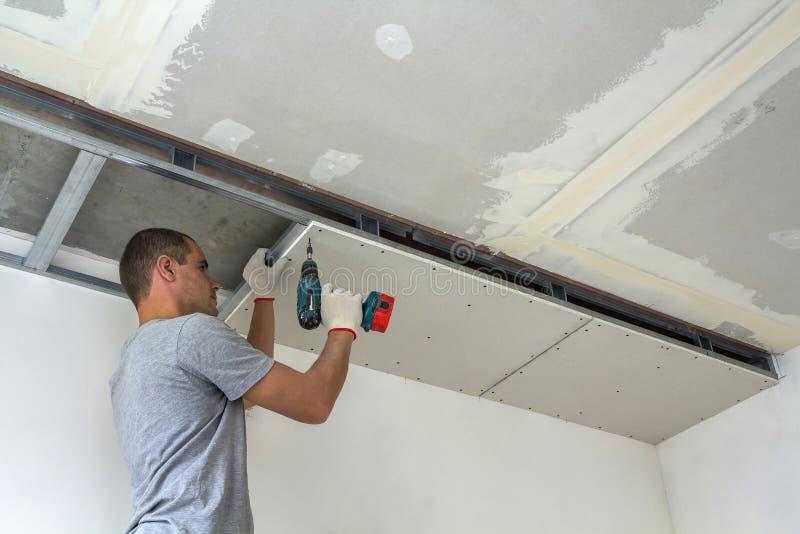 Byggnadsarbetaren monterar ett inställt tak med den drywallen royaltyfri fotografi