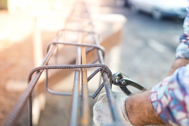 Byggnadsarbetaren räcker säkrande av stålstänger med trådstången för förstärkning av betong royaltyfri foto