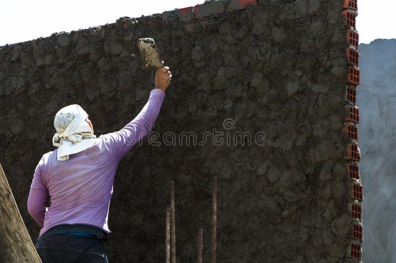 Byggnadsarbetaren - rappa och släta betongväggen med cement vid en stålmurslev - spateln arrangera i rak linje arkivfoto