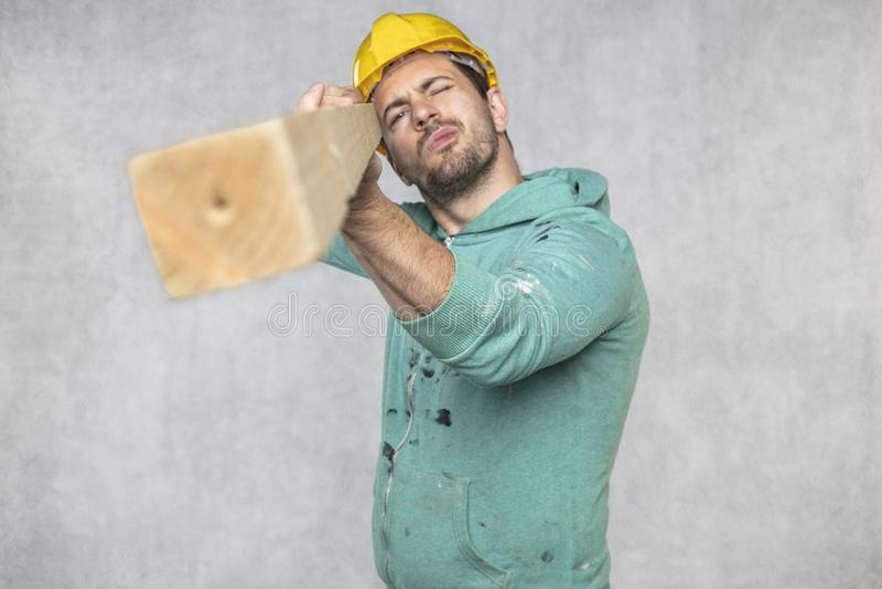 Byggnadsarbetaren rymmer ett stycke av brädet i hans händer, begreppet av att välja trä för konstruktion royaltyfria bilder