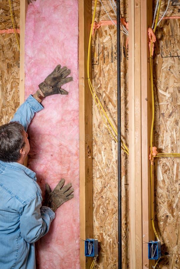Byggnadsarbetaren sätter upp någon isolering mellan dubbar arkivfoto