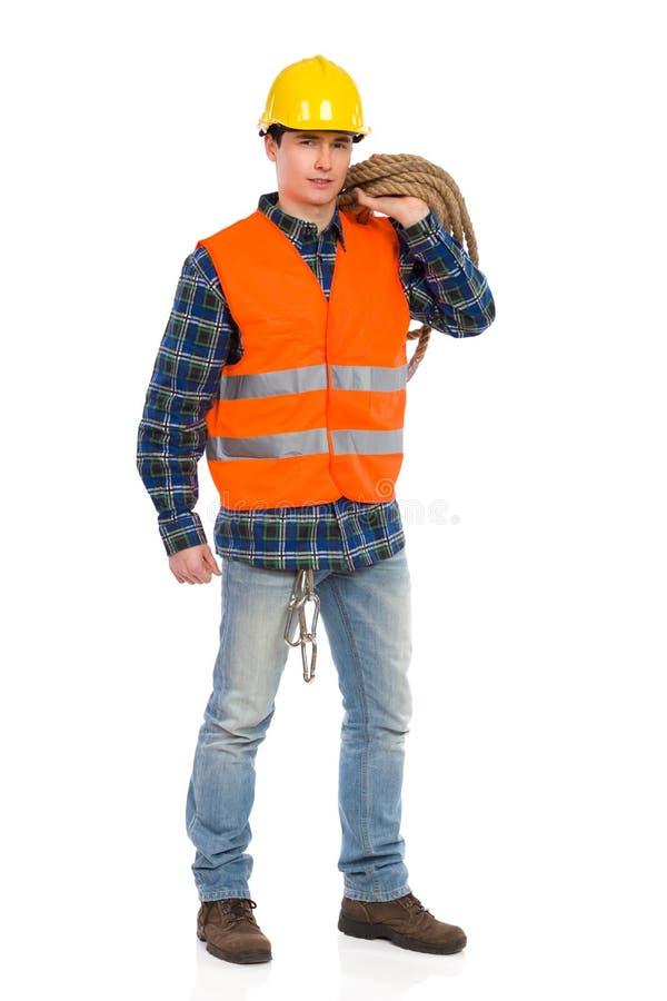 Byggnadsarbetaren som bär reflekterande kläder, och innehavet buntar repet. arkivfoto