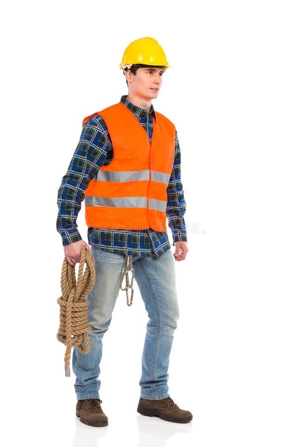 Byggnadsarbetaren som bär reflekterande kläder, och innehavet buntar repet. arkivbilder