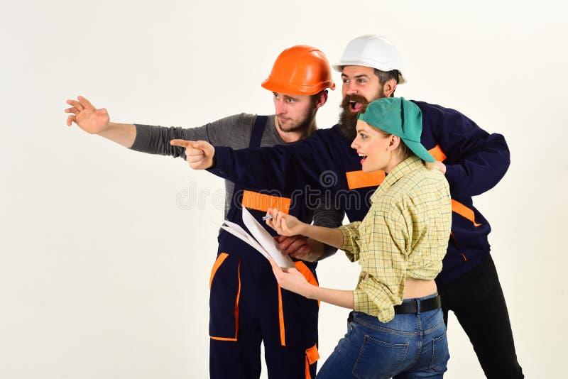 Byggnadsförhållanden Män och kvinnabyggmästare som arbetar i lag Grupp av konstruering av teknikerer och av arkitekter på arbete royaltyfria bilder