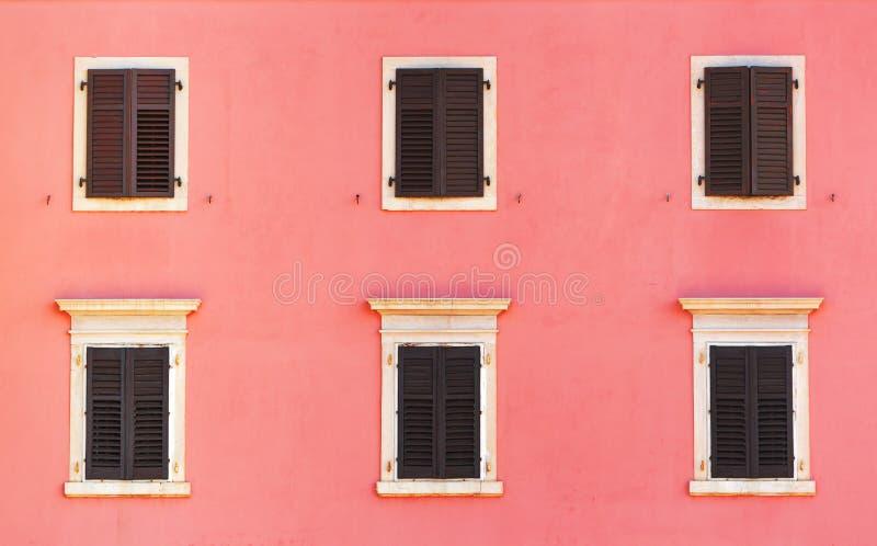 Byggnadsfasad och gamla fönster med klassisk träslutarebli royaltyfria bilder
