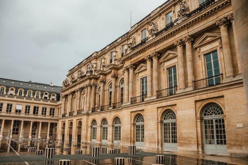 Byggnadsfasad och inre borggård med folk på regnig dag på Palais-Royal i Paris royaltyfria foton