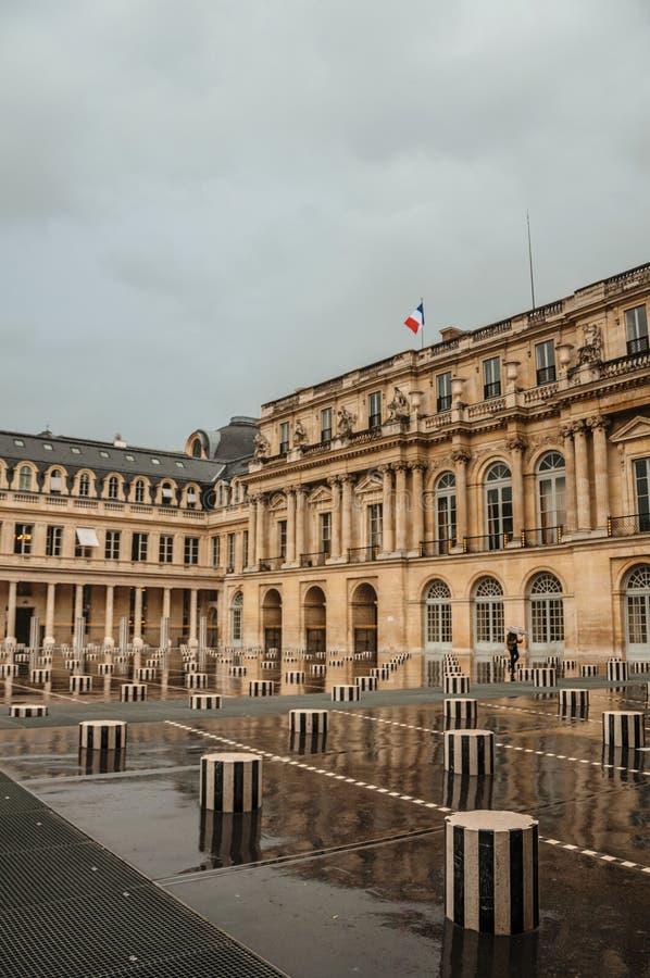 Byggnadsfasad och inre borggård med folk på regnig dag på Palais-Royal i Paris royaltyfria bilder