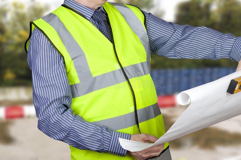 Byggnadsinspektör i hög kraft som kontrollerar platsplan som rymmer andenivån royaltyfri foto