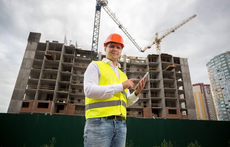 Byggnadsinspektör med den digitala minnestavlan på konstruktionsplats arkivfoton