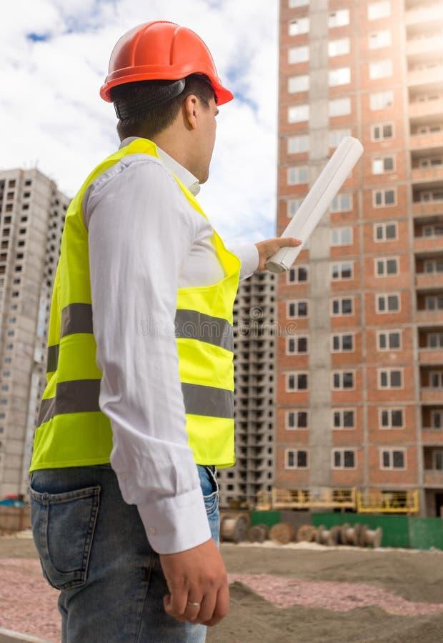 Byggnadsinspektör som pekar på byggnad under konstruktion royaltyfria bilder