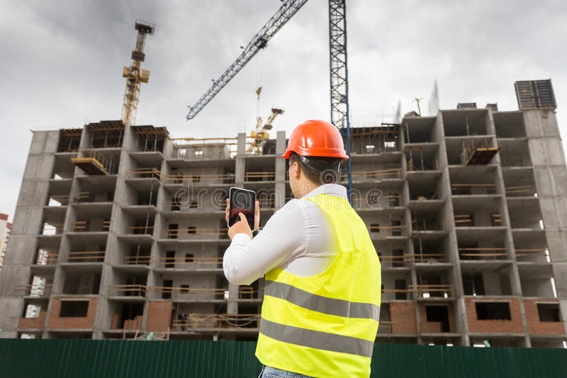 Byggnadsinspektör som rymmer den digitala minnestavlan och kontrollerar buildin royaltyfri fotografi