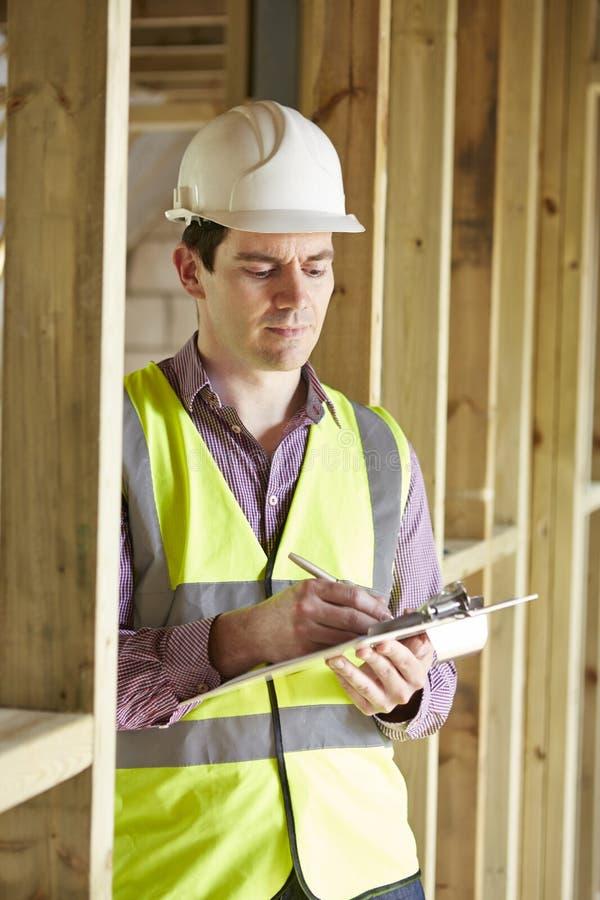Byggnadsinspektör som ser den nya egenskapen arkivbild