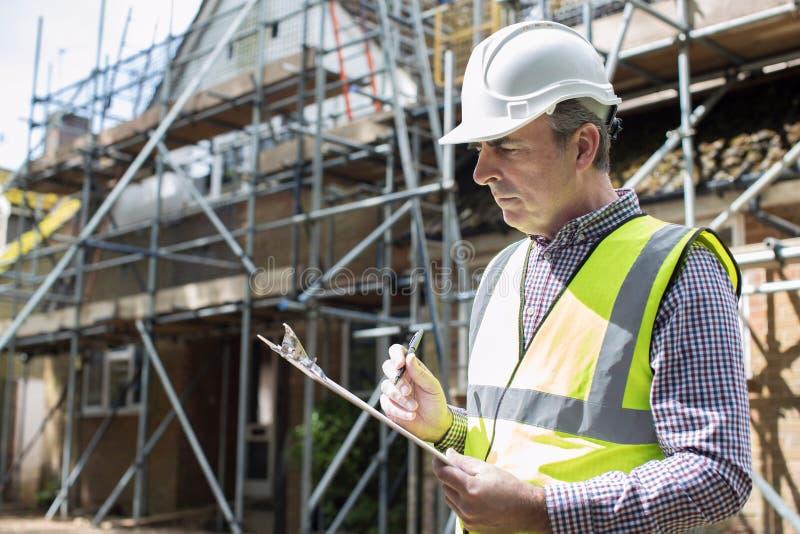 Byggnadsinspektör som ser husrenoveringprojekt royaltyfria bilder