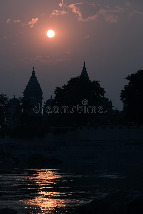Byggnadskontur på solnedgången i Indien Solreflexion på floden för dublin för bilstadsbegrepp litet lopp översikt Orchha tempelko royaltyfria foton