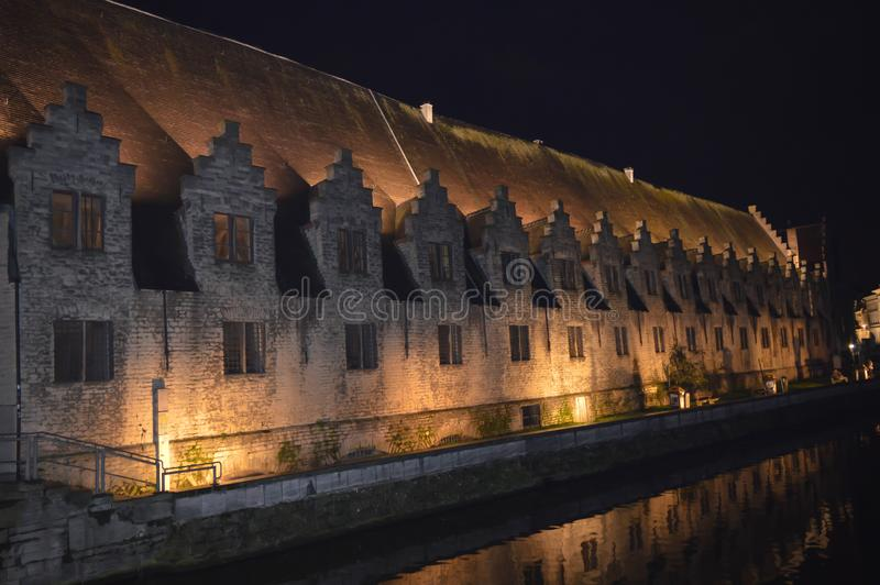 Byggnadsnattsikten reflekterade på vatten i Ghent, Belgien på November 5, 2017 arkivfoto
