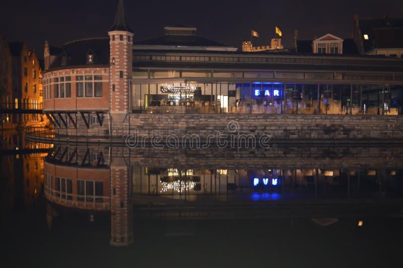 Byggnadsnattsikten reflekterade på vatten i Ghent, Belgien på November 5, 2017 arkivfoton