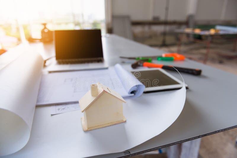 Byggnadsritning- och husmodell på tabellseminarium fotografering för bildbyråer