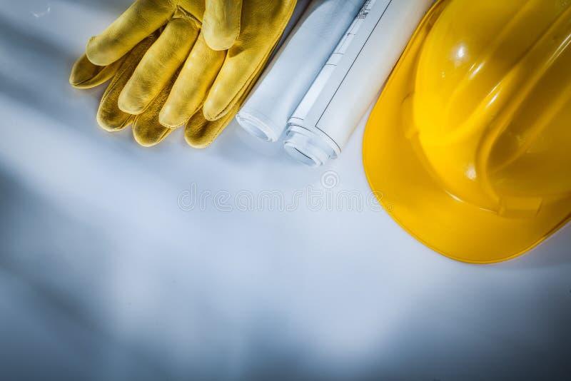 Byggnadsritningar som bygger hjälmsäkerhetshandskar på vitbac arkivbild