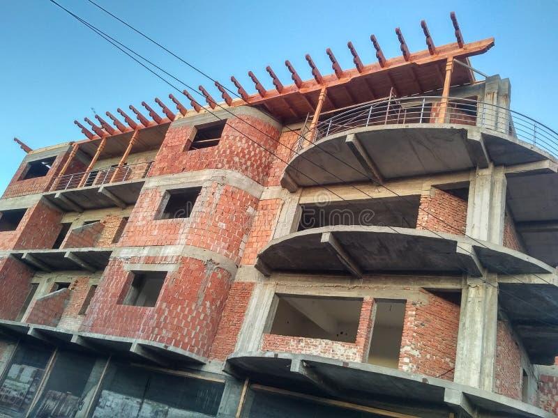 Byggnation av bostadsblock, betong och murar av tegel, träelement för tak och blå himmel i bakgrunden fotografering för bildbyråer