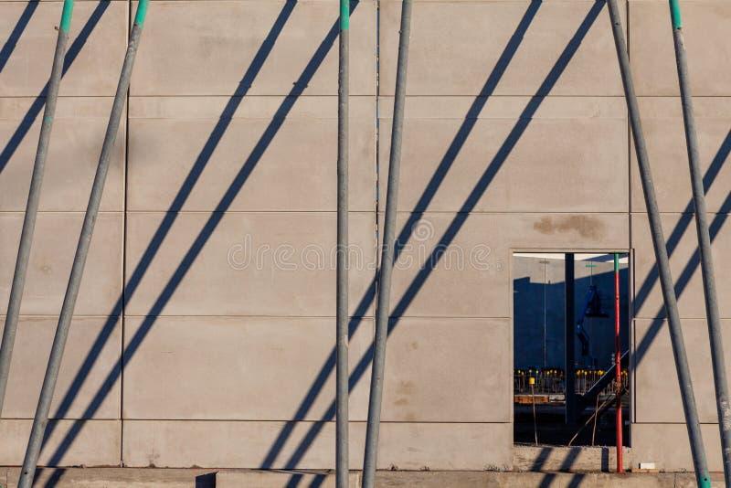Byggplatscen med stöd som håller upp en ny betongvägg royaltyfria bilder