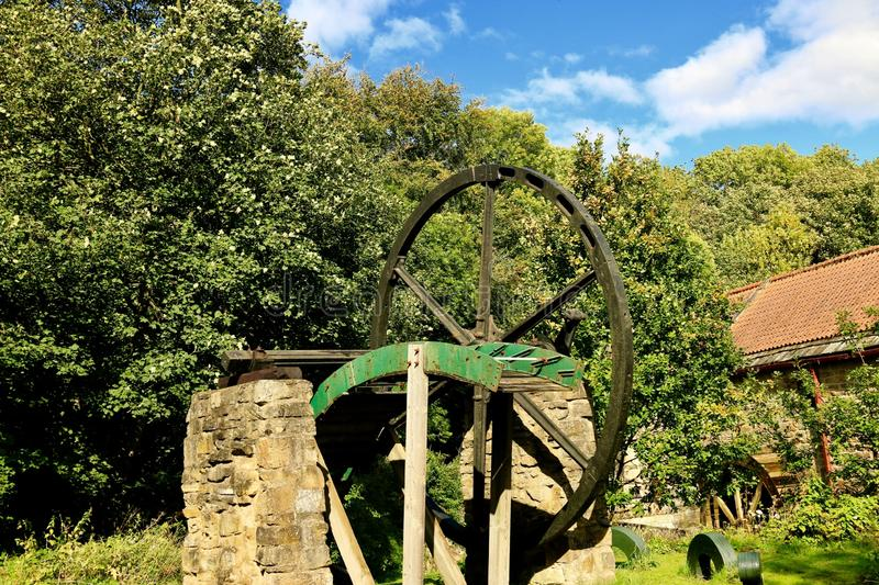 Bygone age of water power 1782. The drive wheel and part of Watermill reminents of a bygone age set on old stone pillars with the restored Watermill in the stock photography