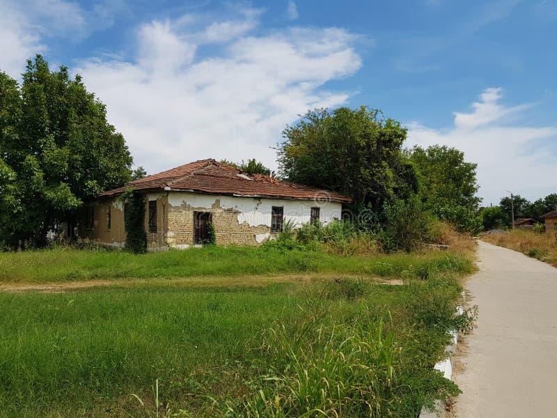Byhus bredvid vägen mellan träd, gräs och himmel royaltyfri bild