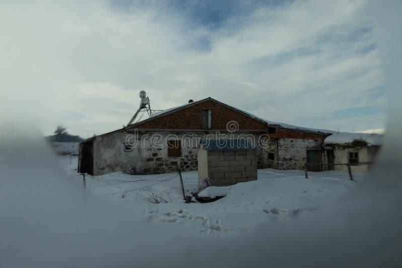 Byhus i snön arkivfoto