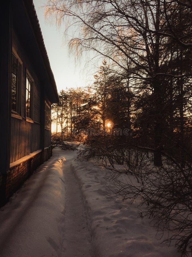 Byhus i vinter i afton arkivfoto