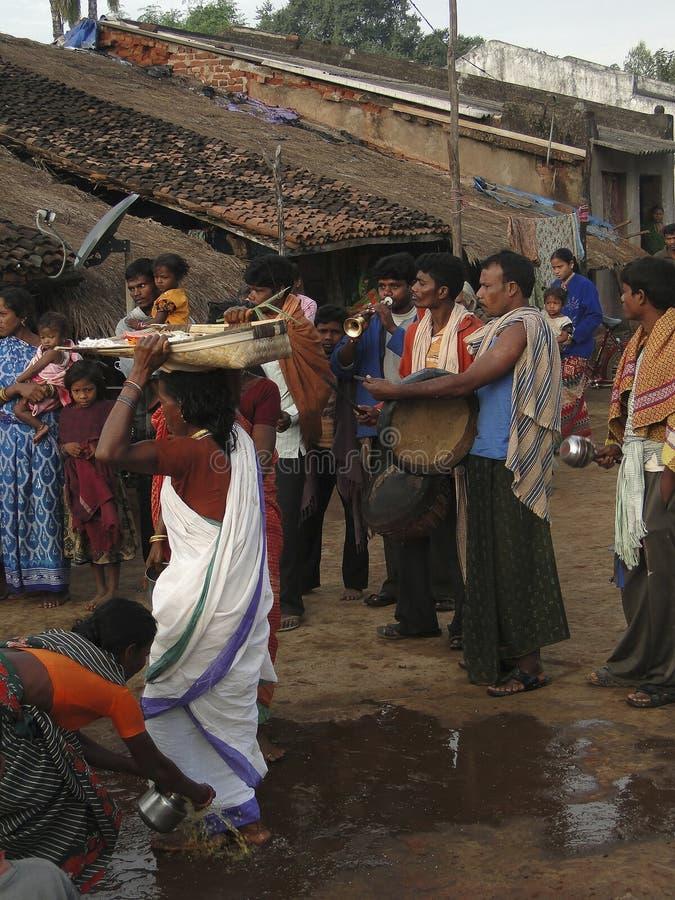 Byinvånare och musiker deltar i besöket av en priestess royaltyfri bild
