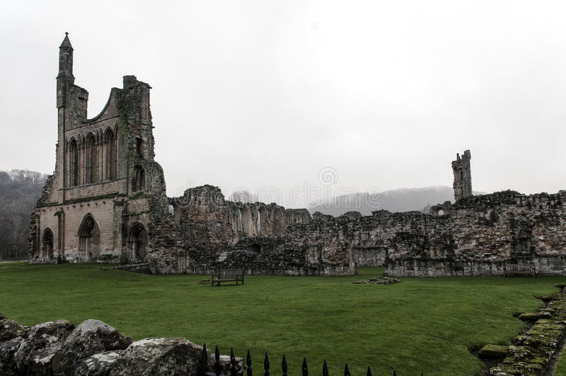 Byland Abbey With Mist i träd arkivfoto