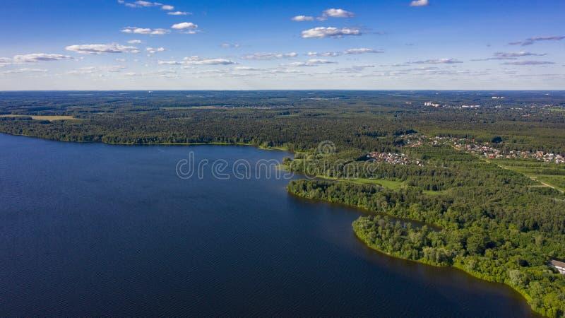 byn i skogen nära sjön med stackmolnmoln royaltyfria bilder