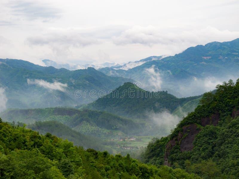 Byn sedd thorugh fördunklar runt om berget fotografering för bildbyråer
