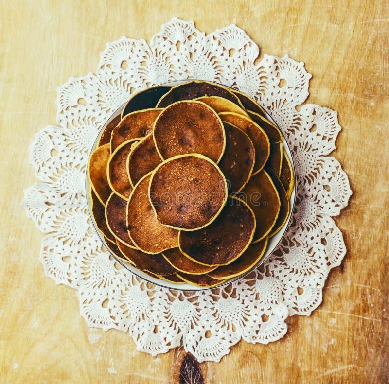 Bypannkakor på träbakgrund på mönstrade servetter royaltyfri foto