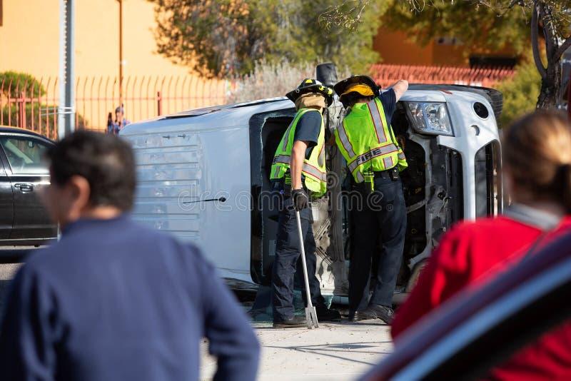 Bystanders beobachten Notfallreaktoren, wie sie einen abgestürzten Minibus löschen stockbilder
