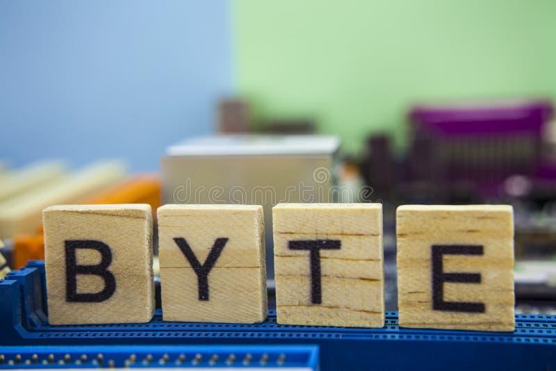 BYTE da palavra nos blocos de madeira com fundo do mainboard dos computadores Fundo da tecnologia da informação com mainboard imagem de stock